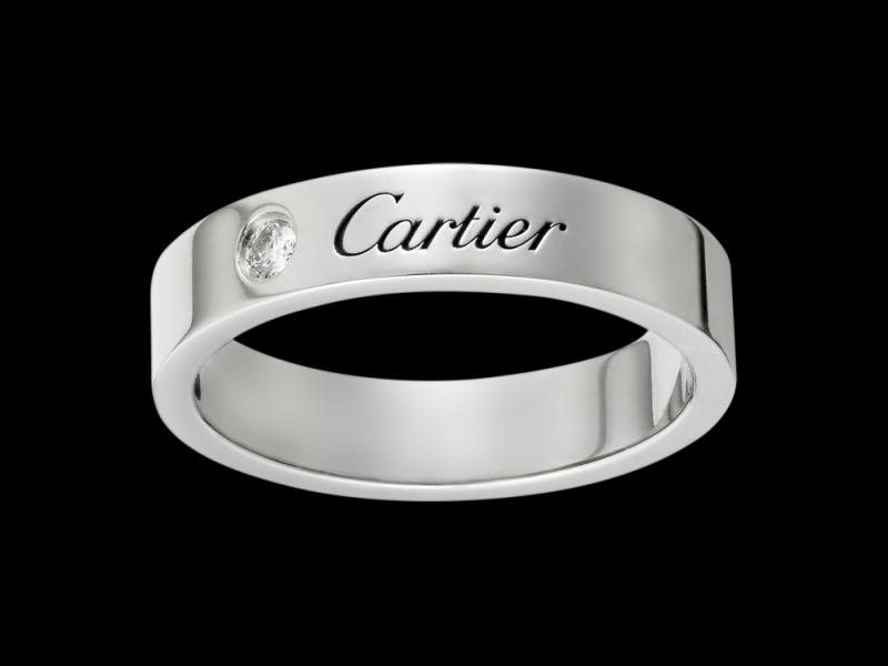 Cartier- Alliance Gravée A simple platinum engraved Cartier wedding band with a diamond set next to the brand name. (~ 2'960 Euros)