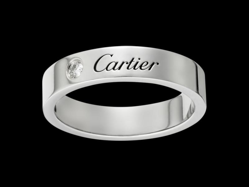 Cartier- Alliance Gravée A simple platinum engraved Cartier wedding band with a diamond set next to the brand name. (~ 2'960 Euros)