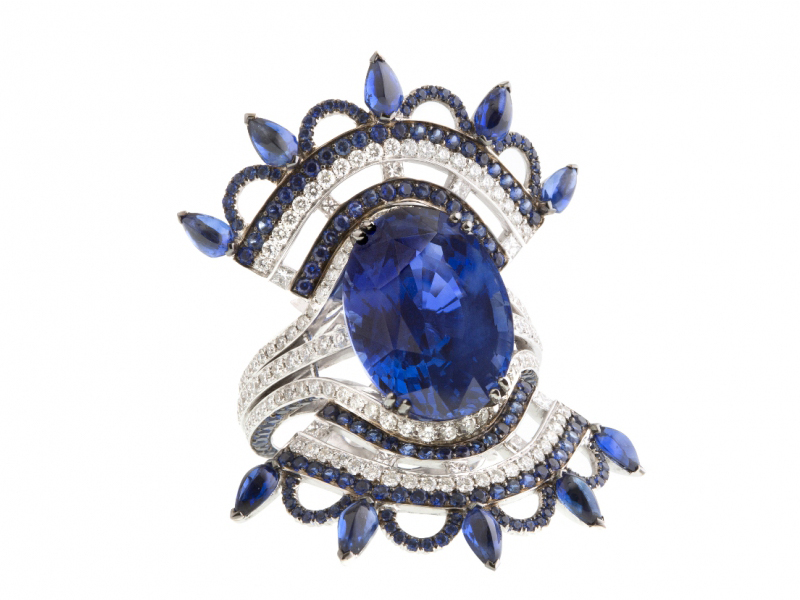 John Rubel BLEU CARMEN RING This ring is made of white gold, sapphires and diamonds. The 12,74 carats vivid blue natural Sapphire is from Ceylon This piece is a tribute to the « Rockette brooch » created by John Rubel in 1945, and reinterpretes the ballerina dresses. The Carmen ring is one of the masterpieces of the New Collection launched in Paris in September 2015.