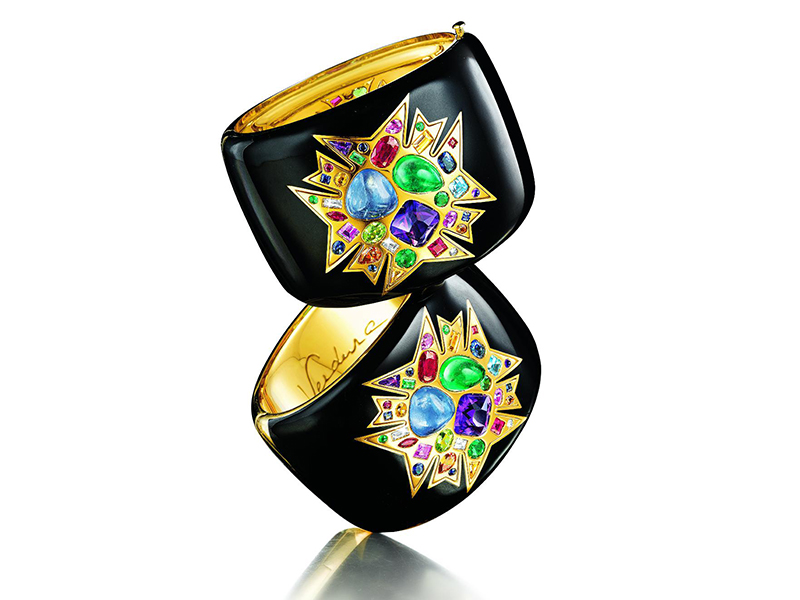 """THEODORA CUFF A centered trio of sapphire, emerald, and amethyst in high relief, surrounded by rubies, diamonds, aquamarines, garnets, citrines and peridot, set in 18k gold, on a hinged cuff of black enamel over gold. Limited series of 200, sold in pairs or individually, engraved with a number and """"Verdura New York, 1939"""""""
