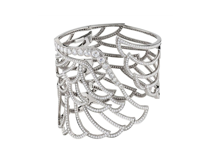 Garrard An 18 carat white gold large lace design bangle from the Wings 10th Anniversary collection, set with round brilliant cut diamonds and rose cut diamond edge.