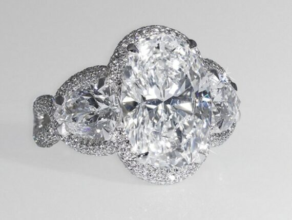 David Morris Oval diamond mounted with pear-shape diamond shoulders and micro-set white diamonds